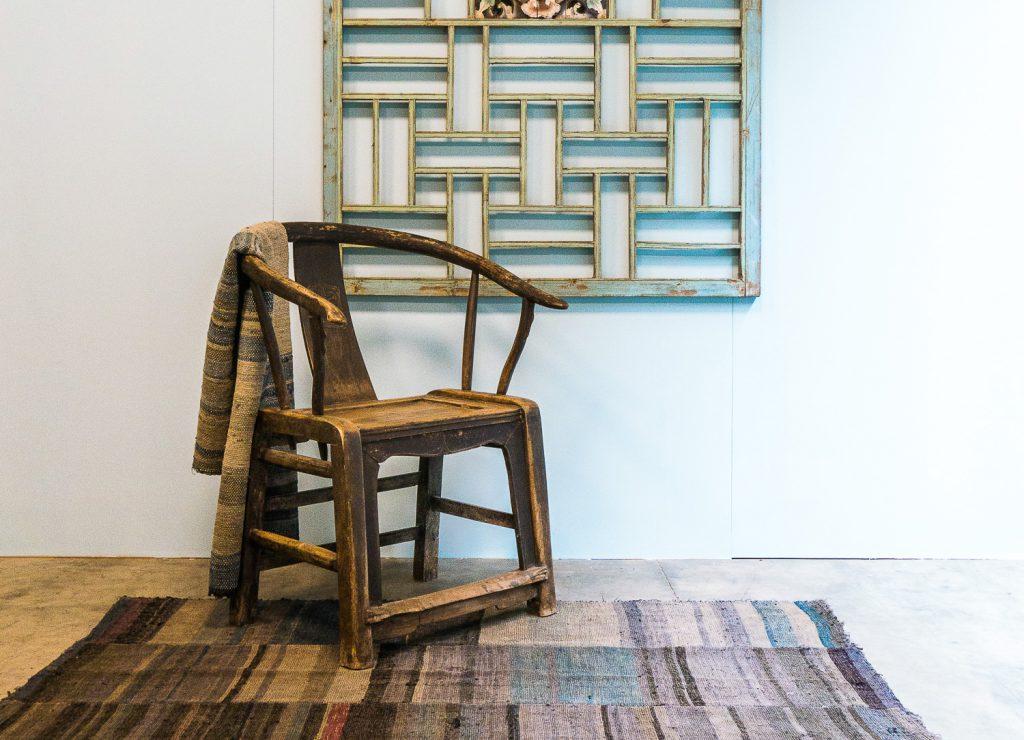 Antieke hoefijzerstoel op een oud tapijt van de Yao minderheidstam, en een decoratief oud houten paneel aan de muur