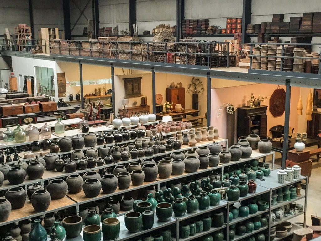 Het magazijn van de Zijderoute Collectie met veel antieke meubels en stapels antieke potten