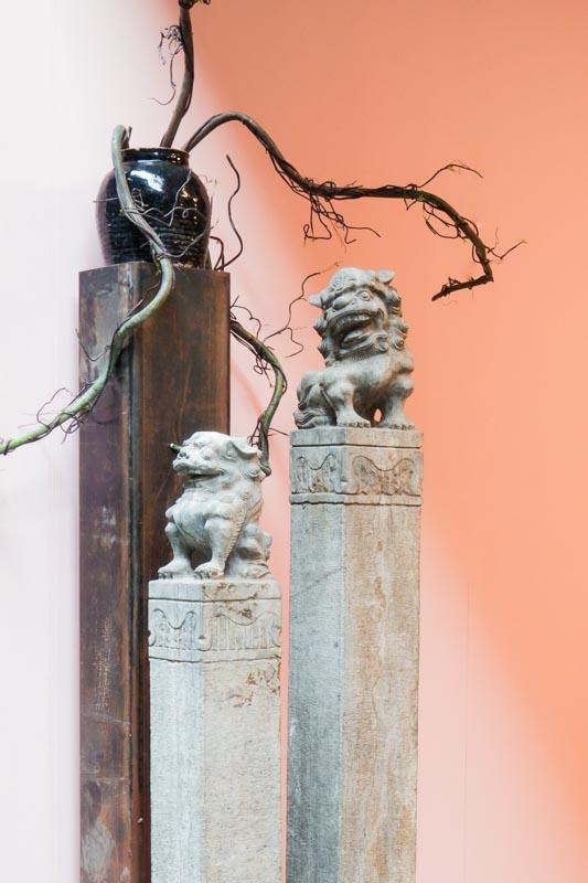 Chinese Fu Dog palen met leeuwenkoppen gemaakt van steen, met een oude zwarte pot versierd met vaantjes