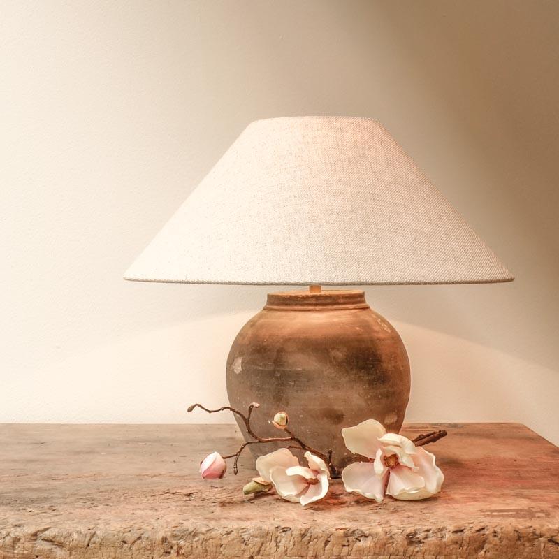 Oude Chinese keramische pot in landelijke stijl die is omgevormd tot een lamp, met een decoratieve bloem ervoor