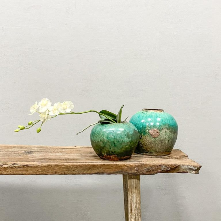 Antique turquoise ginger pot with decorative flowers standing on a weathered Chinese wooden bench